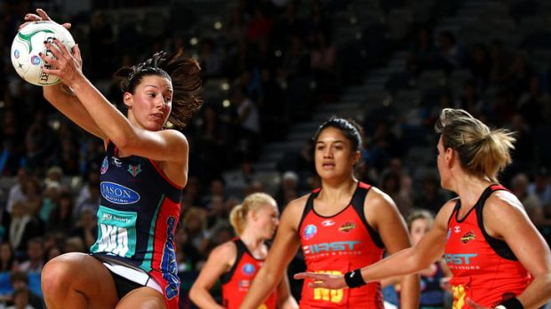 Madison Browne of the Melbourne Vixens (left) leaps to grab a pass in front of two Waikato Bay of Plenty Magic opponents ...