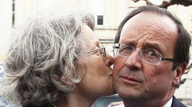 Front runner ... Francois Hollande, right, is kissed by a supporter in Tulle. The Socialist challenger was expected to ...