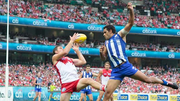 On song: Sydney's Craig Bird beats North Melbourne's Daniel Wells to the ball.