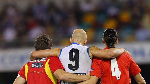 Hop it: Gary Ablett is helped from the ground.