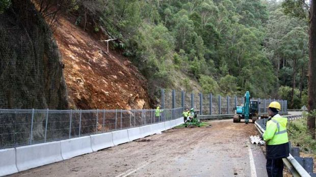 Race to reopen ... workers fix fencing following the landslide on the Kings Highway.