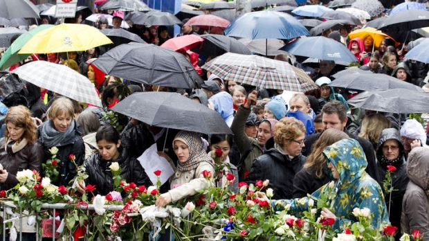 People gather beside flower decked railings as they participate in a protest during which the gathering sang a song ...