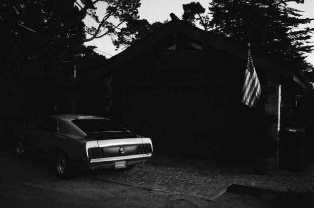The rear end of a Ford, Mustang parked in the driveway of a home flying the American flag in Carmel, California.