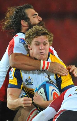 Big hit … Michael Hooper is tackled by Josh Strauss.