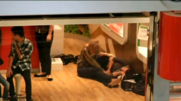 A woman is comforted after the shooting in the Robina Town Centre.