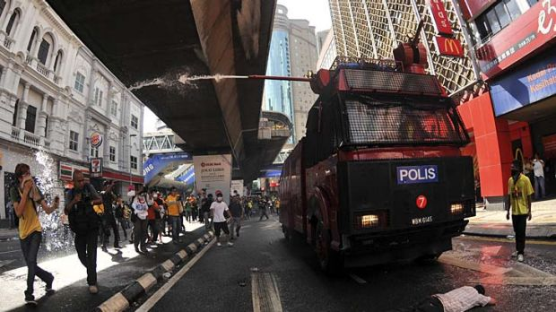 A protester lies in front of a water cannon truck during a rally to demand for electoral reforms in Kuala Lumpur, ...