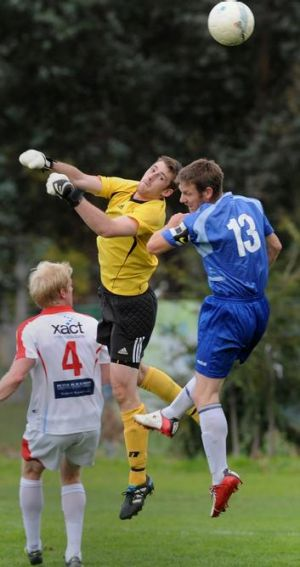 Canberra Olympic goalkeeper James Bradbury  heads the ball clear of Woden Valley's Ben Pagett and Olympic's Robbie ...