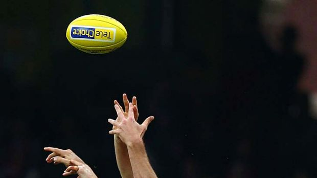 Ted Richards and Heath Grundy of the Swans compete for the ball against Hamish McIntosh of the Kangaroos.