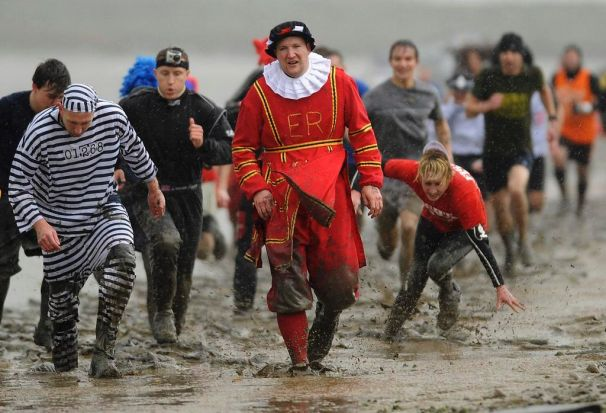 Competitors run in the rain along the banks of a the Blackwater River at low tide during the Maldon Mud Race in Maldon