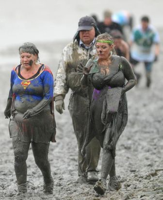 Competitors run in the rain along the banks of a the Blackwater River at low tide during the Maldon Mud Race