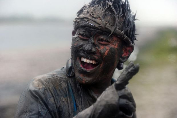 A competitor laughs after taking part in the Maldon Mud Race in Maldon, Essex