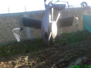 Part of a damaged helicopter is seen lying near the compound after US Navy SEAL commandos killed bin Laden .