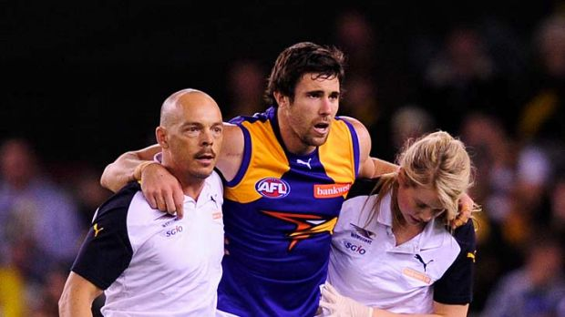 West Coast worries: Josh Kennedy is helped from the field after injuring his ankle.