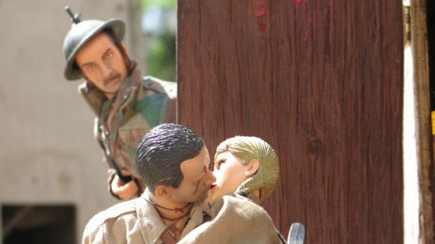 A soldier looks on as the Marwencol-ised Hogancamp and his bride steal a kiss.
