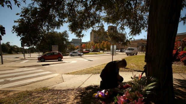 A hospital worker looks at flowers that are left at the scene of an accident outside The Canberra Hospital.