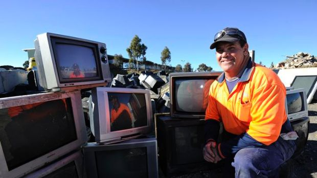 Mitchell Transfer Station's Doug Bailey with the old TVs that have been dropped off to be recycled.