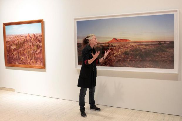 Rosemary Lang, in front of her large outback photograph.