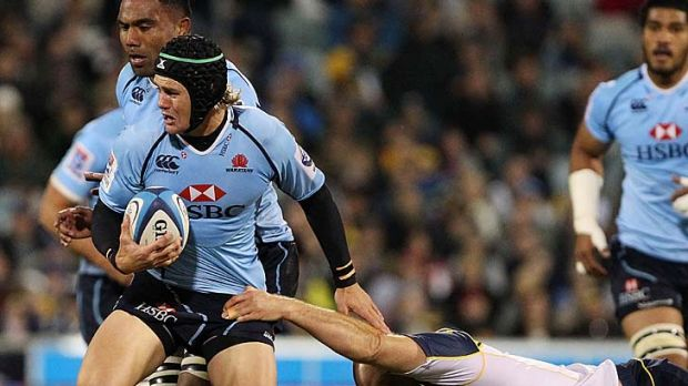 Berrick Barnes of the Waratahs is tackled by Stephen Moore of the Brumbies.