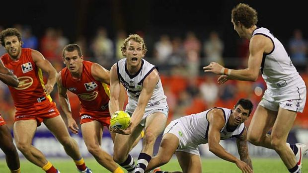 Here it comes: David Mundy clears the pack and handballs to teammate Michael Barlow yesterday.
