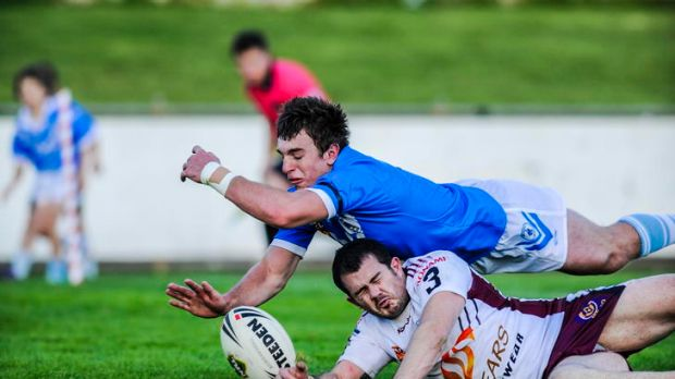 Kangaroos player Matt Adam and Blue Tyson Endacott dive for the ball during yesterday's local derby.