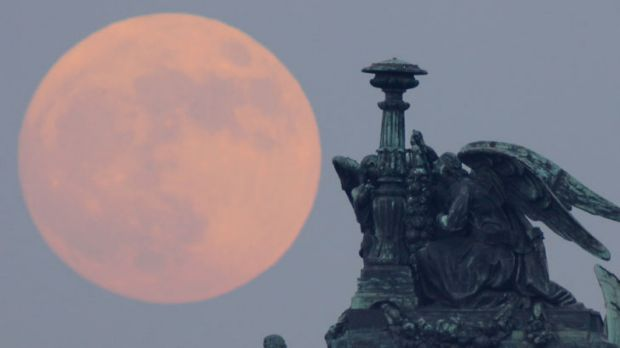 Super-sized: The full moon rises behind statues of angels fixed at the St Isaak's Cathedral in St Petersburg, Russia ...