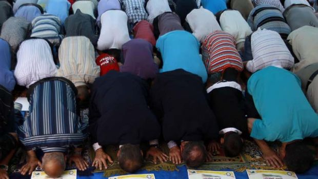 Well supported ... Palestinians pray next to pictures of Palestinian prisoners involved in hunger strikes.