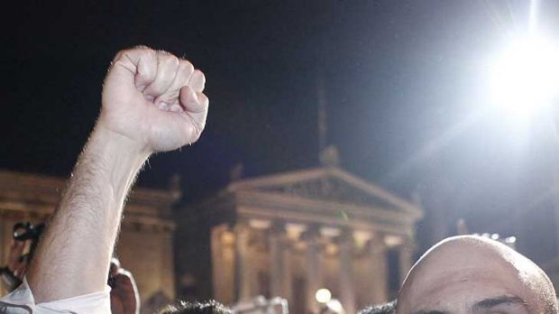 Powering ... Left Coalition party leader Alexis Tsipras greets supporters with a clenched fist after the elections. He ...