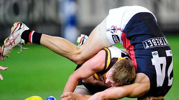 Head first: Hawthorn's Sam Mitchell goes in low against St Kilda's Sean Dempster on Saturday night.