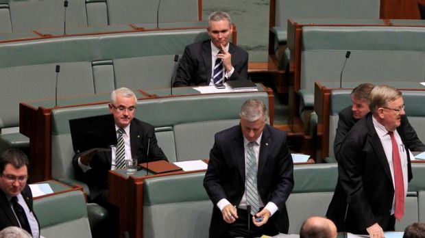 Independent MP Craig Thomson remains seated top as coalition and Andrew Wilkie, left, rise to vote to suspend him from ...