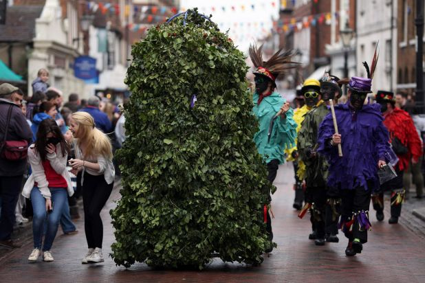 Children chase the 'Jack-in-the-Green' down the high street during the annual Sweeps Festival.