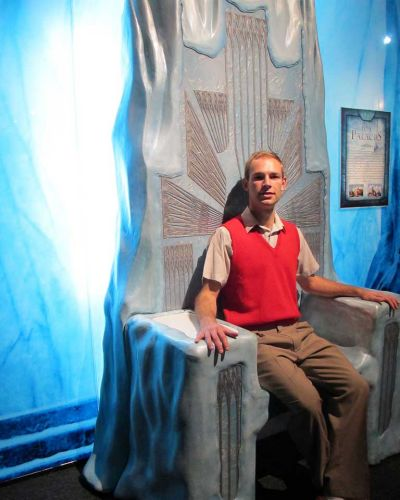 An actor playing Peter Pevensie sits in the White Witch's throne.