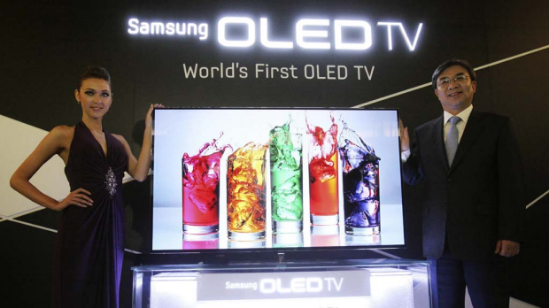 Kim Hyun-suk, head of Samsung's TV business, right, and a model pose with a 55-inch Samsung OLED TV at the launch.