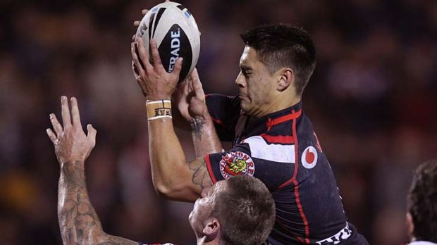 Shaun Johnson of the Warriors leaps over Shaun Kenny-Dowall to score his second try.