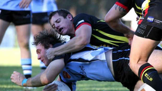 Belconnen United Scholars player Brent Crisp gets tackled during the match at West Belconnen Leagues Club.