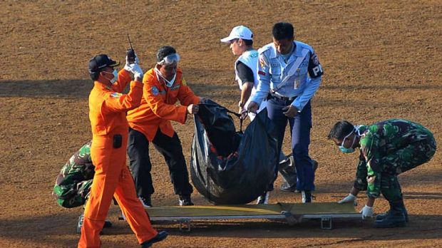 Human remains ... a rescue team carry a body bag.