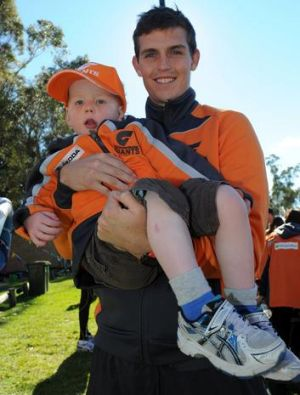 Giants' Phil Davis with two-year-old fan Lachlan McLeod at the Giants fan day at ANU South Oval on Sunday.