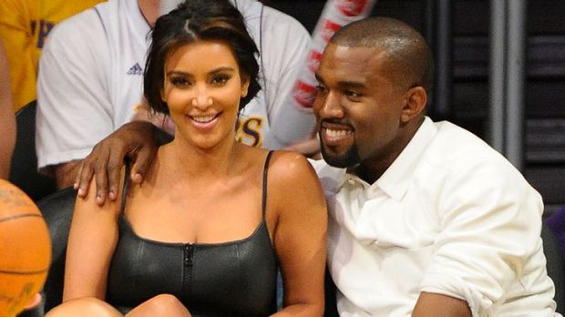 Famous curves ... Kim Kardashian and rumoured new beau, rapper Kanye West, get cosy at a basketball game.