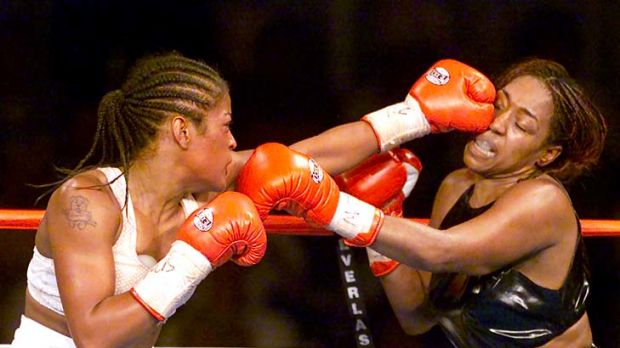Laila Ali, (left) the 23-year-old daughter of boxing legend Muhammad Ali, lands a left jab to the head of 39-year-old ...