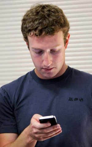 A Facebook phone, maybe ... Mark Zuckerberg  checks his mobile phone for messages.
