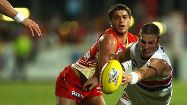 On their knees: Gold Coast's Dion Prestia and Bulldog Matthew Boyd vie for possession in the slippery conditions in ...