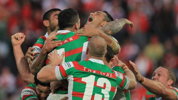 Souths players mob Adam Reynolds after his golden point field goal.