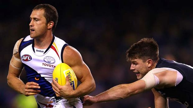 Frustrated Blues: Adelaide's Jason Porplyzia marks in front of Carlton's Bryce Gibbs.