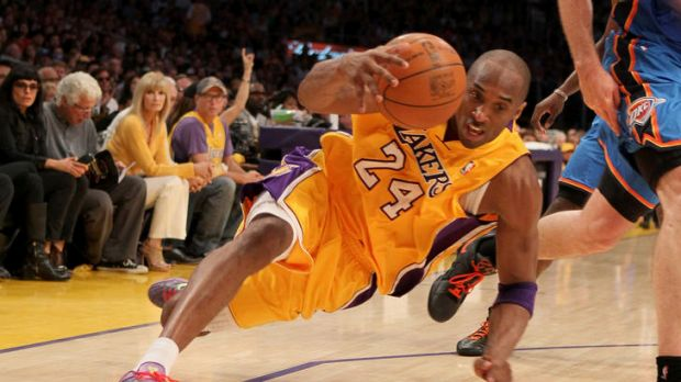 Kobe Bryant of the Los Angeles Lakers falls as he dribbles the ball in the second quarter while taking on the Oklahoma ...