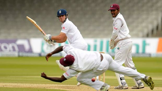 Alastair Cook cuts a delivery past Darren Sammy as Denesh Ramdin looks on.
