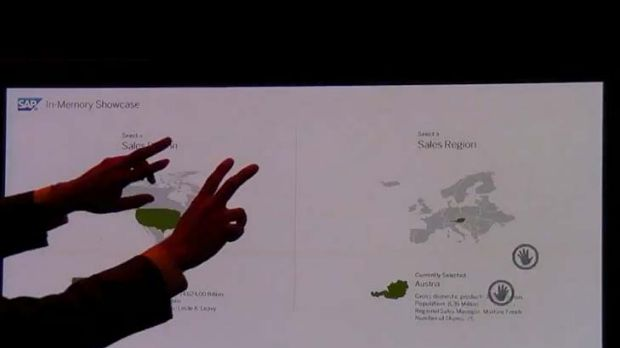 A man uses both hands to change screens and demonstrate SAP's HANA in a video demonstration. He can highlight regions on ...