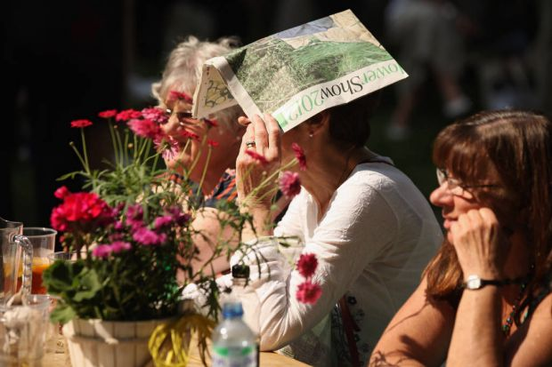 Visitors to the Royal Horticultural Society's Chelsea Flower Show relax in the sunshine.