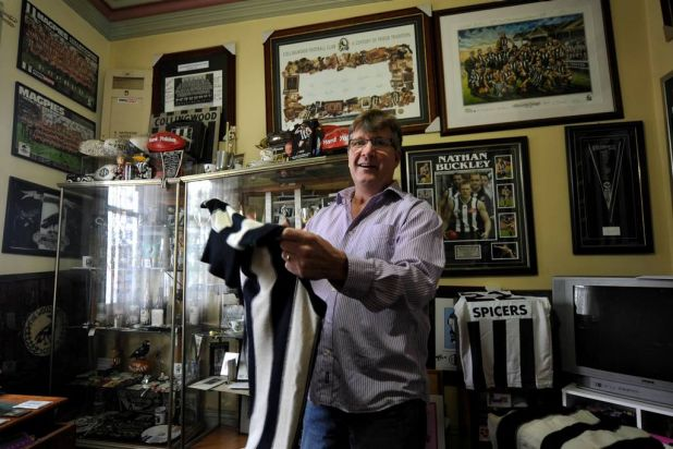 Former Collingwood footballer Cameron Doyle with a jumper that belonged to Magpies great Len Thompson.