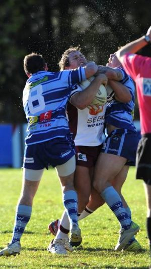 Queanbeyan's Troy Whiley is tackled by Warriors duo Brent Turner, left, and Tom Robins.
