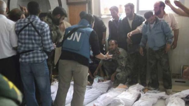 High emotion … UN observers at a morgue after the massacre of more than 92 people, including 32 children, in the ...