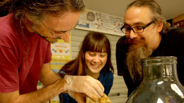 Scientist Cameron Wilson and State Library of Queensland staff with the beginnings of a new fabric.